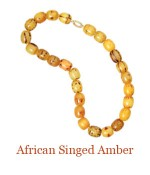 These African beads are singed amber. Each individual bead has its own special design made by the woman's husband and given to her as a token of his love.  The beads are hand tied and secured with a handsome oval continuous loop 14k clasp  -overall length   $1,400.00
